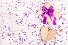 Bright gift box with satin bow and wooden heart on a white background with rhinestones.  St. Valentine`s Day Royalty Free Stock Images