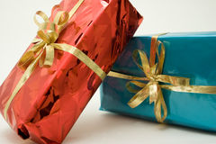 Bright Gift Packages. Bright and Shiny Red and Blue Gift Boxes with Gold Ribbon Bow royalty free stock photos