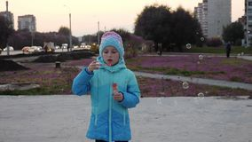 A bright girl in a blue jacket inflates soap bubbles and lets them through the wind. stock video footage