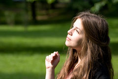 Bright girl in park. Beautiful girl in park is looking at the sun with luxurious hair Royalty Free Stock Images