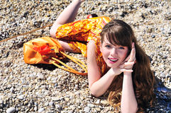 Bright girl on the pebble Stock Photography