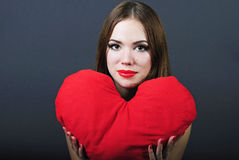 Bright girl with pillow heart in hand Royalty Free Stock Photos