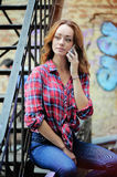 Bright girl in  plaid shirt talking on the phone. Bright girl in a plaid shirt talking on the phone, the youth of today Stock Image