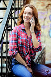 Bright girl in  plaid shirt talking on the phone. Bright girl in a plaid shirt talking on the phone, the youth of today Stock Images