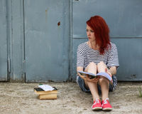 Bright girl with red hair. Student with books and notebooks sitting on a wall background. Stock Images