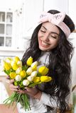 Bright girl with a smile in the kitchen with а yellow tulips in the kitchen royalty free stock photo