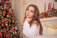 A bright girl in a sweater and a skirt is waiting for the New Year`s miracle. New Year`s themed shooting of the girl in anticipation of the New Year`s miracle Royalty Free Stock Image
