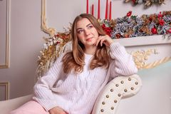 A bright girl in a sweater and a skirt is waiting for the New Year`s miracle. New Year`s themed shooting of the girl in anticipation of the New Year`s miracle Royalty Free Stock Photo