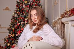 A bright girl in a sweater and a skirt is waiting for the New Year`s miracle. New Year`s themed shooting of the girl in anticipation of the New Year`s miracle Stock Images