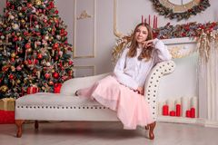 A bright girl in a sweater and a skirt is waiting for the New Year`s miracle. New Year`s themed shooting of the girl in anticipation of the New Year`s miracle Stock Photo