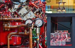 Bright glasses next to complex machine with many gauges and pipe royalty free stock photography