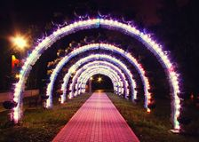 Bright glowing arch of colored lanterns in the park in the evening Royalty Free Stock Photos