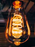 Bright glowing clear glass lamp pear shaped close up. Illumination edison retro lamp dark background. Antique vintage. Filament light bulb. Abstract industrial royalty free stock images