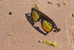 Bright gold color sunglasses in the wet sand, beach Stock Photo