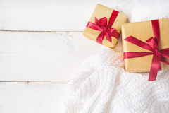 Bright gold  presents with red ribbon on wood background Royalty Free Stock Photo
