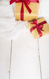 Bright gold  presents with red ribbon on wood background Stock Image