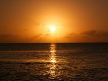 Bright gold sunset with ocean reflection royalty free stock photo