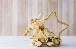 Bright golden christmas star ornament with oak leaves and jingle. Bells on a rustic wooden background stock photo