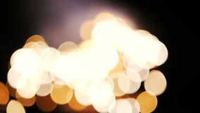 Bright golden lights shimmer in the blured background. Glare from sparks stock video footage