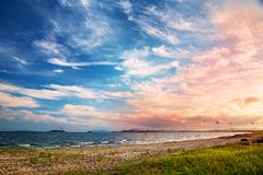 Bright golden sunset on the beach, the waves on the sand, shells. Setting sun Royalty Free Stock Image