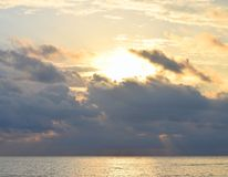 Bright Golden Yellow Sunlight from Dark Grey Clouds in Sky spreading over Ocean with Reflection in Water - Skyscape. This is a photograph of bright golden yellow stock photos