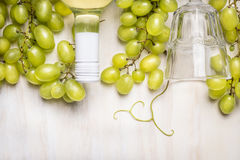 Bright grapes with a bottle of white wine and glass on rustic  a white wooden background Royalty Free Stock Photo