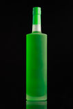 Bright green alcohol bottle. On black background Royalty Free Stock Images