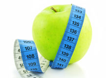 Bright green apple and measuring tape isolated. On a white background Royalty Free Stock Photography
