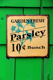 Bright green background with colorful metal sign selling Parsley Stock Photography