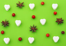 Bright green background with sugar heart, anise stars and cranberries. Green background with sugar heart, anise stars and cranberries. Top view Royalty Free Stock Image