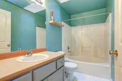 Bright green blue Bathroom with white tub and shower combo. Bright green blue Bathroom interior with light gray bathroom vanity and white tub and shower royalty free stock photos
