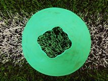 Bright green blue plastic cone on painted white line. Plastic football green turf playground with grind black rubber Royalty Free Stock Photography