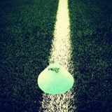 Bright green blue plastic cone on painted white line. Plastic football green turf playground with grind black rubber in core. Dram Stock Image