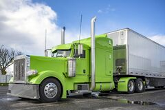 Free Bright Green Classic American Idol Big Rig Semi Truck Tractor With Shiny Chrome Parts And High Vertical Exhaust Pipes And Dry Van Royalty Free Stock Photo - 215119475