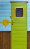 Bright Green Door. A bright lime green door, with a yellow window framing a bead curtain, on a turquoise and wood trailer Royalty Free Stock Photo