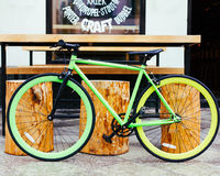Bright green Fixed Gear beautiful vintage bicycle stands Next to the city`s hipster pub. Outdoor stock photography