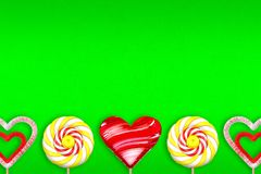 Brightly green background with various lollipops. 3d illustratio. Bright green gradient background with various lollipops. Lollipop in the shape of heart Royalty Free Stock Photo