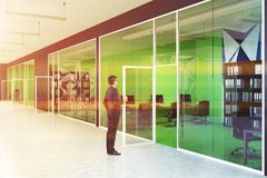 Bright green modern office and lobby, businessman. Young businessman standing in a bright green office interior with a geometric wall pattern and rows of Royalty Free Stock Image