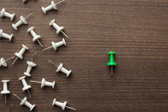 Bright green push pin out of the crowd Royalty Free Stock Image