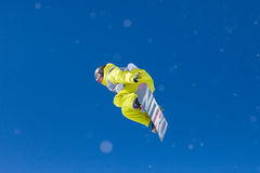 Bright Green Snowboarder Mid Air Side View. Snowboarder competing in competition in Val Thorens, France Royalty Free Stock Photo