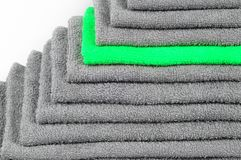 Bright green terry towel in stack of other gray ones. colour contrast stock images