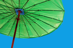 Bright green umbrella against a blue sky stock photos