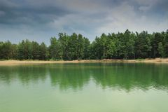 Bright green water and dark blue sky after rain royalty free stock photo