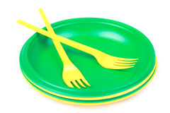 Bright green and yellow plastic disposable tableware, plates and. Forks, on white background close-up Royalty Free Stock Photography