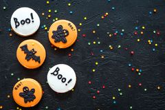 Halloween gingerbread cookies with pictures of bat, ghost on black background top view copyspace. Bright halloween gingerbread cookies on black background top stock photo