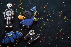 Halloween gingerbread cookies with pictures of bat, skeleton on black background top view copyspace. Bright halloween gingerbread cookies on black background top stock photos