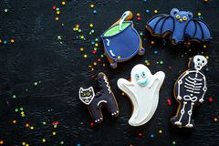 Halloween gingerbread cookies with pictures of bat, skeleton on black background top view copyspace. Bright halloween gingerbread cookies on black background top stock images