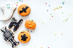 Halloween gingerbread cookies with pictures bat, pumpkin, skeleton, ghost on white background top view copyspace. Bright halloween gingerbread cookies on white stock photos