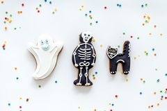 Halloween gingerbread cookies with pictures bat, skeleton on white background top view copyspace. Bright halloween gingerbread cookies on white background top royalty free stock image