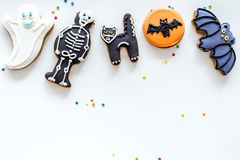 Halloween gingerbread cookies with pictures bat, skeleton, ghost on white background top view copyspace. Bright halloween gingerbread cookies on white background royalty free stock images